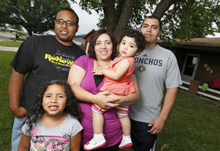 Kaylee Sanchez, 6, her father Eli Sanchez, mother Maria Sanchez, sister Ellie Sanchez, 1, and uncle Miguel Blanco pose for a photo in front of the Sanchez's home in the Plaza Towers housing addtion in Moore. Photo by Nate Billings, The Oklahoman NATE BILLINGS - NATE BILLINGS