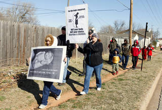 Angela Jeffers of Moore and Stephanie Tarlton of Oklahoma City carry signs as they walk down Western Avenue Monday while participating in the 2013 March for Life OKC from Our Lady's Cathedral, 3214 N Lake Ave., to the state Capitol building. PAUL B. SOUTHERLAND - PAUL B. SOUTHERLAND
