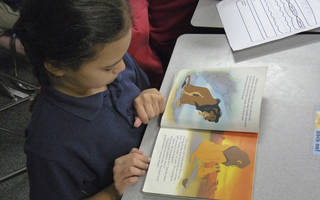 "Mark Twain Elementary second-grader Cienna Johnson, 8, reads ""The Lion King"" while waiting for her classmates to finish work. Oklahoma Watch photo."
