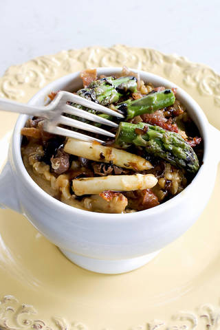 Creamy brown rice risotto with asparagus and tomatoes. Matthew Mead - AP