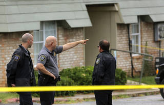 Police officers secure a crime scene at the Villas at Stone Lake Apartments on the morning of July 16. Two people were found shot inside a Ford F150 pickup truck in one one of the parking lots outside the apartments, said police Master Sgt. Gary Knight. One victim was found dead at the shooting scene, and the second victim died at the hospital. Photo by Jim Beckel, The Oklahoman.