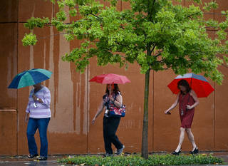 Women stay dry under umbrellas as they walk through downtown Oklahoma City during a recent rain storm. Photo by Chris Landsberger, The Oklahoman CHRIS LANDSBERGER - CHRIS LANDSBERGER