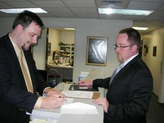 State Election Board Secretary Paul Ziriax, left, goes over filing papers Wednesday with Kenneth Meador, a Democratic candidate for the Senate District 43 seat. Michael McNutt - THE OKLAHOMAN