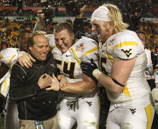 West Virginia Mountaineers linebacker Hunter Bittner (54) and offensive linesman Pat Eger (76) hug head coach Dana Holgorsen, left, after defeating Clemson 70-33 at the Orange Bowl NCAA college football game Thursday, Jan. 5, 2012, in Miami . (AP Photo/Lynne Sladky) ORG XMIT: SLS129