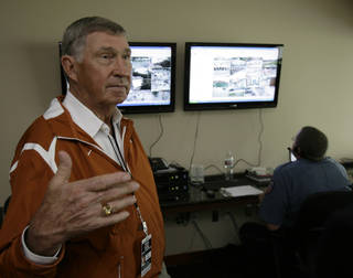 In this photo taken Saturday, Oct. 10, 2009, University of Texas athletics director DeLoss Dodds, foreground, explains the workings of the stadium security video monitor area before a Longhorns NCAA college football game in Austin, Texas. In the background, officer W.R. Pieper views a myriad of camera angles around the stadium. (AP Photo/Harry Cabluck)
