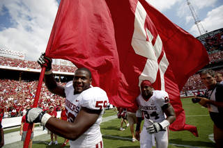 Oklahoma's Donald Stephenson (59) carries a flag in front of Oklahoma's Frank Alexander (84) after the Red River Rivalry college football game between the University of Oklahoma Sooners (OU) and the University of Texas Longhorns (UT) at the Cotton Bowl in Dallas, Saturday, Oct. 8, 2011. Oklahoma won 55-17. Photo by Bryan Terry, The Oklahoman ORG XMIT: KOD