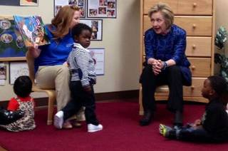 Former Secretary of State Hillary Clinton (right) reads with teacher Brittany Holland (left) and youngsters from Tulsa Educare during a classroom visit on Monday. MATT BARNARD/Tulsa World