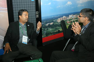 Manu Nair, left, talks with a visitor at the Biotechnology Industry Organization convention in San Diego. Photo by Jim Stafford -