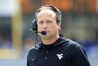 West Virginia coach Dana Holgorsen looks on during the second quarter of an NCAA college football game against Georgia State in Morgantown, W.Va., on Saturday, Sept. 14, 2013. West Virginia won 41-7. (AP Photo/Christopher Jackson) ORG XMIT: WVCJ111