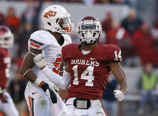 BEDLAM FOOTBALL / CELEBRATION: Oklahoma's Aaron Colvin (14) celebrates breaking up a pass intended for Oklahoma State's Josh Stewart (5) during the Bedlam college football game between the University of Oklahoma Sooners (OU) and the Oklahoma State University Cowboys (OSU) at Gaylord Family-Oklahoma Memorial Stadium in Norman, Okla., Saturday, Nov. 24, 2012. OU won 51-48 in overtime. Photo by Sarah Phipps, The Oklahoman