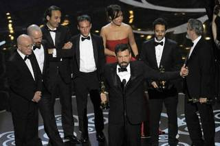 "Director/producer Ben Affleck, center, accepts the award for best picture for "" Argo,"" as the cast and crew look on during the Oscars at the Dolby Theatre on Sunday Feb. 24, 2013, in Los Angeles. (Photo by Chris Pizzello/Invision/AP)"