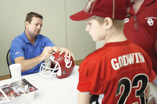 OU football coach Bob Stoops signs a helmet for Zac Godwin, 9, of Yukon, during the Sooner Caravan stop at the National Cowboy & Western History Museum on Thursday. (Photo by Bryan Terry, The Oklahoman)