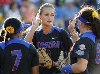 Florida pitcher Hannah Rogers (13) celebrates with teammates, including Kelsey Stewart (7) and Bailey Castro, between innings during Game 5 of the Women's College World Series softball tournament between Florida and Oregon at ASA Hall of Fame Stadium in Oklahoma City, Friday, May 30, 2014. Photo by Nate Billings, The Oklahoman