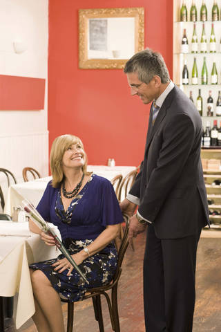A man holds a chair for a woman in a restaurant. Jupiterimages