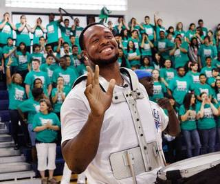 As students and faculty cheer and clap in background, Gerald McCoy flashes a smile and waves to students seated on the other side of the gymnasium after he finished playing the drums. McCoy entered the gym playing a drum with members of the Oklahoma City Thunder drum section. Oklahoma native and professional football player Gerald McCoy spoke to students at his alma mater, Southeast High School, Friday afternoon, May 20, 2011. At the end of his remarks, he announced he is donating some drums to the band and new uniforms for the school's marching band, too. Photo by Jim Beckel, The Oklahoman JIM BECKEL