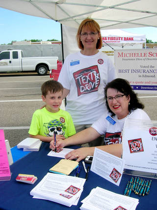 """Michelle Schaefer, insurance agent, watches as Joan Curtis, right, signs a pledge not to text and drive. With Curtis is her son John, 6. The Saturday event, called """"Mommy Please Don't Text & Drive,"""" was held near the Oklahoma Fidelity Bank on E Second Street in Edmond. Photo by Steve Gust, For The Oklahoman -"""