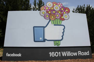 Flowers were added to a Facebook sign Sunday in front of Facebook headquarters in Menlo Park, Calif. AP Photo