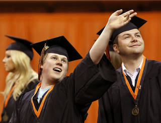 Eric Humphreys of Grandview, TX, waves to someone seated in the arena as he marches in the procession with fellow graduating students. Undergraduates at OSU participated in the school's 127th commencement ceremony the weekend of Friday, May 3 and Saturday, May 4, 2013 inside Gallagher-Iba Arena on the university's campus.These photos were taken at the Saturday morning ceremony when students from the College of Agricultural Sciences and Natural Resources, and the Spears School of Business were conferred with degrees. Photo by Jim Beckel, The Oklahoman.