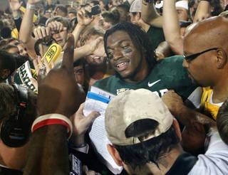 Baylor's Robert Griffin III (10) is surrounded by fans as he tries to leave the field after the college football game in which the University of Oklahoma Sooners (OU) were defeated 45-38 by the Baylor Bears (BU) at Floyd Casey Stadium on Saturday, Nov. 19, 2011, in Waco, Texas. Photo by Steve Sisney, The Oklahoman ORG XMIT: KOD