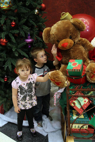 Madelaine and Jaxon McCollough of Mustang check out the presents during the community tree lighting ceremony at the Mustang Town Center on Monday night. PHOTO BY HUGH SCOTT FOR THE OKLAHOMAN ORG XMIT: KOD HUGH SCOTT