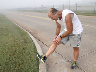 Mike Wall stretches before running along the Interstate 35 service road between 15th Street and Edmond Road near his church, Henderson Hills Baptist Church in Edmond. Photo by Paul Hellstern, The Oklahoman PAUL HELLSTERN -