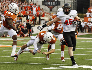 Oklahoma State's Caleb Lavey (45) runs from UT's Joe Bergeron (24), Case McCoy (6) and Kendall Sanders (2) after intercepting the ball in the third quarter during a college football game between the Oklahoma State University Cowboys (OSU) and the University of Texas Longhorns (UT) at Darrell K Royal - Texas Memorial Stadium in Austin, Texas, Saturday, Nov. 16, 2013. OSU won, 38-13. Photo by Nate Billings, The Oklahoman