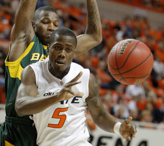 Oklahoma State's Reger Dowell (5) passes the ball in front of Baylor's LaceDarius Dunn (24) during an NCAA college basketball game between Oklahoma State University and Baylor at Gallagher-Iba Arena in Stillwater, Okla., Tuesday, March 1, 2011. Photo by Bryan Terry, The Oklahoman