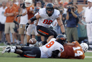 Oklahoma State's Cooper Bassett (80) looks to recover a fumble forced by Daytawion Lowe (8) as Texas' David Ash (14) lies on the ground during fourth quarter of a college football game between the Oklahoma State University Cowboys (OSU) and the University of Texas Longhorns (UT) at Darrell K Royal-Texas Memorial Stadium in Austin, Texas, Saturday, Oct. 15, 2011. Photo by Sarah Phipps, The Oklahoman