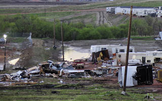 FILE - In this May 27, 2014 file photo, debris is scattered after a tornado hit Watford City, N.D. Authorities say at least eight trailers were destroyed Monday evening when the twister tore through a camp where oil field workers stay. Nine people were injured, including a 15-year-old girl critically. When waves of workers began spilling into western North Dakota for high-paying oil jobs and nowhere to live, they set their eyes on the rural _ and unregulated _ prairie of McKenzie County. The population was booming so fast that no one knew how many people were in the county, so local officials pushed through ordinances that are now being credited in part with helping emergency workers during a severe storm that brought only the 14th tornado to the county in 65 years. (AP Photo/Josh Wood, File)