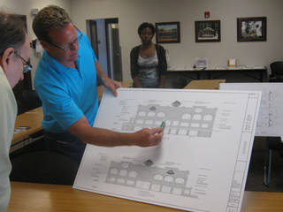 Chris Johnson, center, shows details of his proposed entertainment center to Bricktown Urban Design Committee member Phil MIller. Steve Lackmeyer