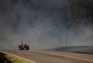 A man drives pass where is home was as grassfire overtakes the area near East Seward Road and Oak Hill Road, Sunday, May 4, 2014. Photo by Sarah Phipps, The Oklahoman