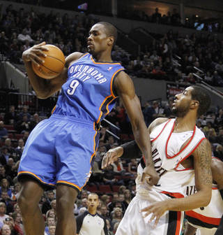 Oklahoma City Thunder forward Serge Ibaka, left, from Congo, hauls in a rebound against Portland Trail Blazers forward LaMarcus Aldridge during the first half of their NBA basketball game in Portland, Ore., Monday, Feb. 6, 2012.(AP Photo/Don Ryan) ORG XMIT: ORDR102