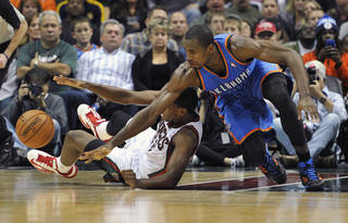 Milwaukee Bucks' Khris Middleton, left, and Oklahoma City Thunder's Serge Ibaka scramble for a loose ball during the second half of an NBA basketball game Saturday, Nov. 16, 2013, in Milwaukee. The Thunder defeated the Bucks 92-79. (AP Photo/Jim Prisching)