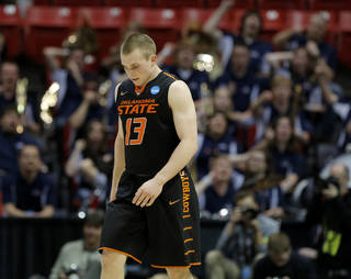 Oklahoma State's Phil Forte (13) walks towards the bench as the Gonzaga band celebrates during a second round game of the NCAA men's college basketball tournament at Viejas Arena in San Diego, between Oklahoma State and Gonzaga Friday, March 21, 2014. Gonzaga won 85-77. Photo by Bryan Terry, The Oklahoman