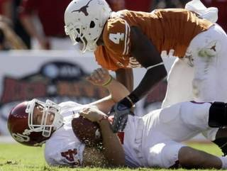 In this photo taken on Saturday, Oct. 17, 2009, Oklahoma quarterback Sam Bradford (14) grimaces in pain while sacked by Texas cornerback Aaron Williams (4) during the first half of an NCAA college football game in Dallas. (AP Photo/Tony Gutierrez)