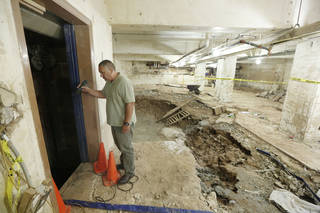 Oklahoma City Public Works Project Manager Mike Arismendez looks at water damage Monday in the basement of the office building at 100 N Walker. The building was heavily damaged during flooding May 31. Photo By Steve Gooch, The Oklahoman Steve Gooch
