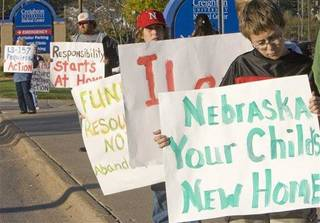 Protesters hold signs in front of the Creighton Medical Center in Omaha, Neb., Thursday, Oct. 16, 2008. AP Photo.