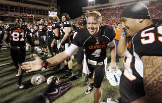 OSU's Brandon Weeden (4) celebrates with his teammates including Tolu Moala (59), right, after the college football game between Oklahoma State University (OSU) and the University of Colorado (CU) at Boone Pickens Stadium in Stillwater, Okla., Thursday, Nov. 19, 2009. OSU won, 31-28. Photo by Nate Billings, The Oklahoman