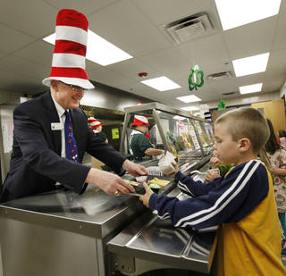 Edmond Public Schools Superintendent David Goin serves green eggs and ham to first-grader Toby Holland at Clegern Elementary School in honor of Dr. Seuss' birthday. PHOTO BY PAUL HELLSTERN, THE OKLAHOMAN. PAUL HELLSTERN - OKLAHOMAN