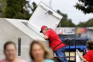 A man looks into a model storm shelter displayed by StraightLine Shelters at the Oklahoma State Fair on Wednesday, Sep. 18, 2013. Photo by Jim Beckel, The Oklahoman.
