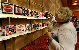 Carol Erikson, of Woods County, photographs some of the 152 quilt blocks made for the Centennial Quilt Block Challenge that commemorates the 100-year history of the Oklahoma Cooperative Extension Service. PHOTO BY STEVE SISNEY, THE OKLAHOMAN STEVE SISNEY