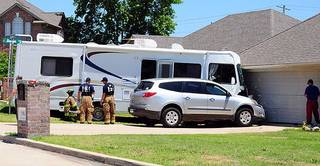 Firefighters look over the scene in Ada after a motor home hit a house when the vehicle's brakes failed. (Ada News photo)