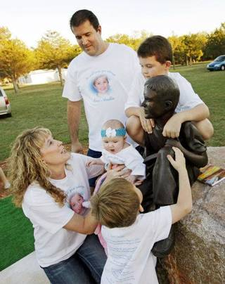 Clockwise from lower left, Renee Haley and Jack Haley, along with son Dalton Haley, 7, daughter Mikayla Haley, 6 months, and son Gabriel Haley, 3, gather around a life-sized statue of their deceased son and brother Austin Haley after the statue was unveiled at the Haley family's home in Noble, Okla., Monday, Oct. 24, 2011. Five-year-old Austin Haley was killed by a Noble police officer's stray bullet in August of 2007. Austin Haley would have been ten years-old on Oct. 24, 2011. Photo by Nate Billings, The Oklahoman ORG XMIT: KOD