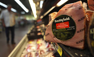 A Smithfield ham is shown at a grocery store in Richardson, Texas. Chinese meat processor Shuanghui International Holdings Ltd. agreed Wednesday to buy Smithfield Foods Inc. for approximately $4.72 billion in a deal that will take the world's biggest pork producer private. AP Photo LM Otero