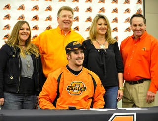 Aledo High Scool lineman Michael Wilson, center, with sister Stephanie, father Mike, mom Becky, mom and Aledo football coach Tim Buchanan smile as Wilson signs a national letter of intent to attend the Oklahoma State and play football during a national signing day event, Wednesday, Feb. 1, 2012, in Aledo, Texas. (AP Photo/The Fort Worth Star-Telegram, Max Faulkner) MAGS OUT ORG XMIT: TXFOR204