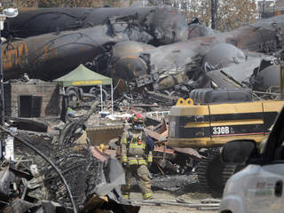 This July 6 file photo shows a worker wearing protective gear moving though the wreckage of the oil train derailment and explosion in in Lac-Megantic, Quebec. Responding to a series of fiery train derailments, federal regulators said Wednesday they will propose that trains transporting crude oil have at least two-man crews and requirements aimed at preventing parked train cars from coming loose and causing an accident like one in July that killed 47 people. Ryan Remiorz - AP