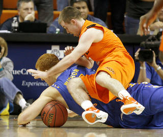 OKLAHOMA STATE UNIVERSITY: Oklahoma's Keiton Page (12) goes for the ball behind Tulsa's David Wishon (15) during an NCAA men's college basketball game between the Oklahoma State Cowboys (OSU) and the Tulsa Golden Hurricane (TU), at Gallagher-Iba Arena in Stillwater, Okla., Wednesday, Nov. 30, 2011. Photo by Bryan Terry, The Oklahoman