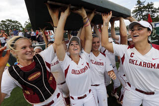 Oklahoma team members Whitney Ellis, Jessica Vest and Lauren Chamberlain and others take an outfield bumper pad to the coach signifying where their banner should go as the University of Oklahoma Sooner (OU) softball team defeats Tennessee in game three of the NCAA super regional at Marita Hynes Field on May 25, 2014 in Norman, Okla. Photo by Steve Sisney, The Oklahoman