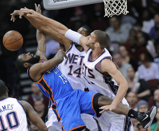 Nets center Brook Lopez, right, and forward Derrick Favors blocks a shot by Thunder guard James Harden. AP PHOTO