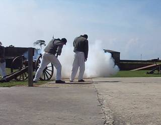 Volunteers in uniforms fire a cannon inside Fort Gaines, one of two forts at the mouth of Mobile Bay.
